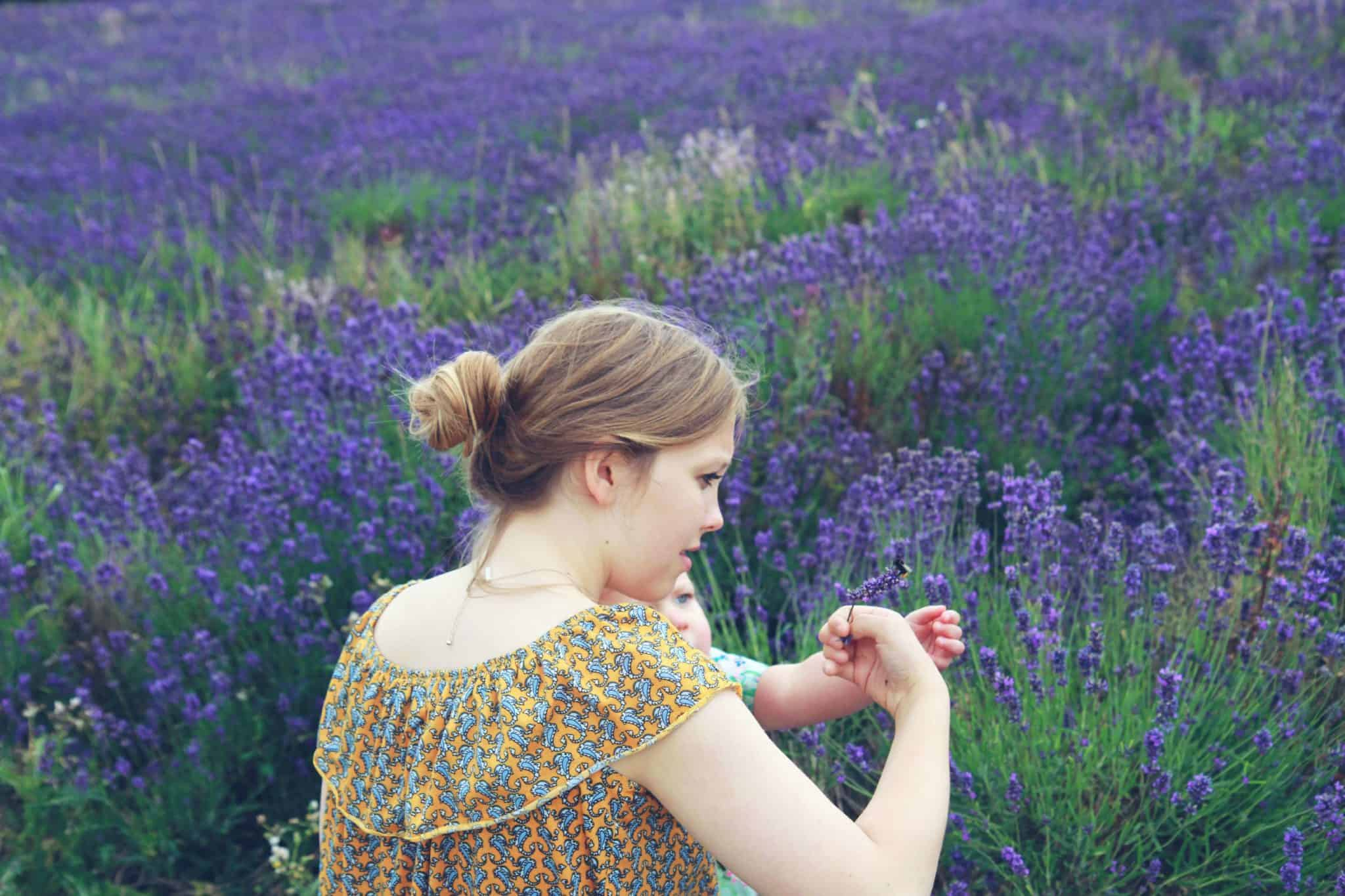 two sisters looking at a bee in a field of lavender