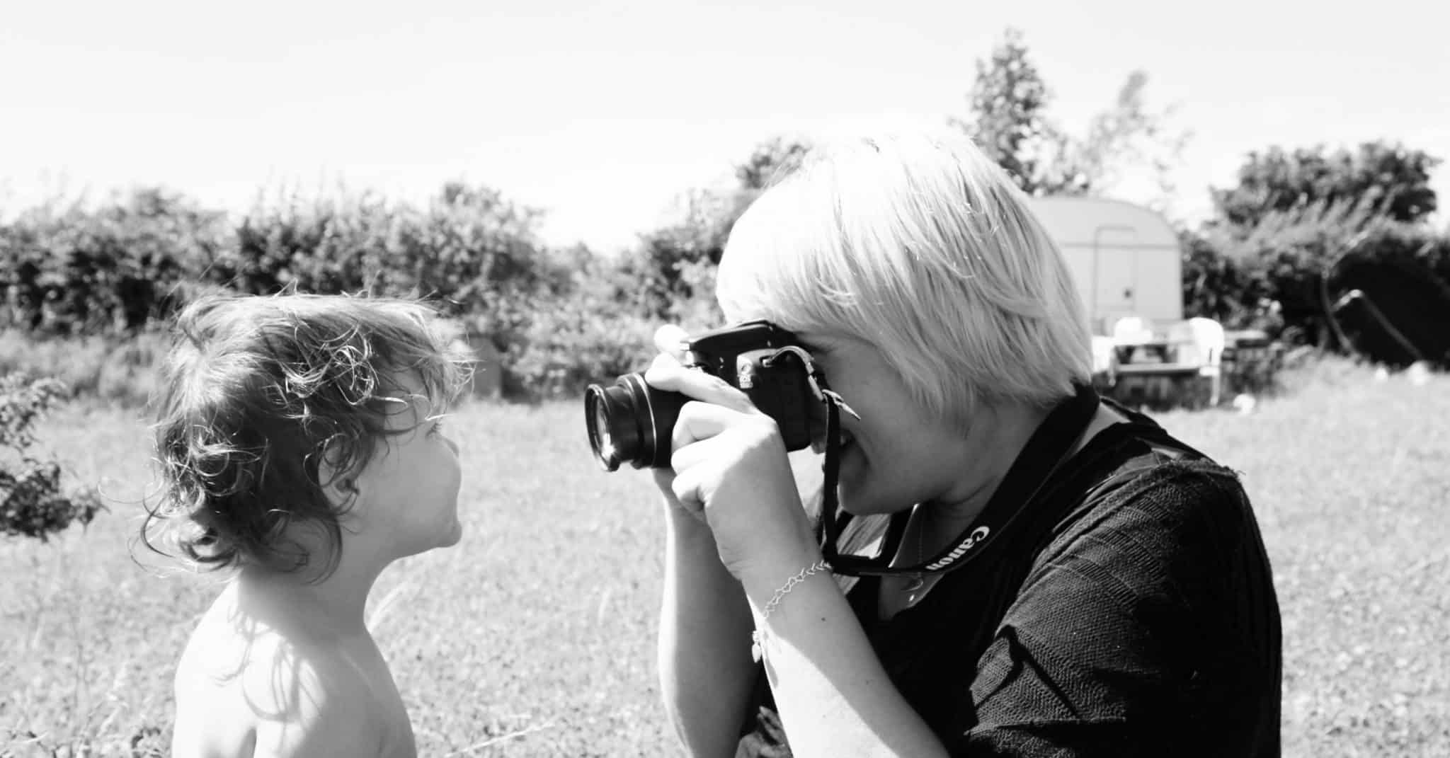 Black and white shot of a toddler having her photograph taken close up