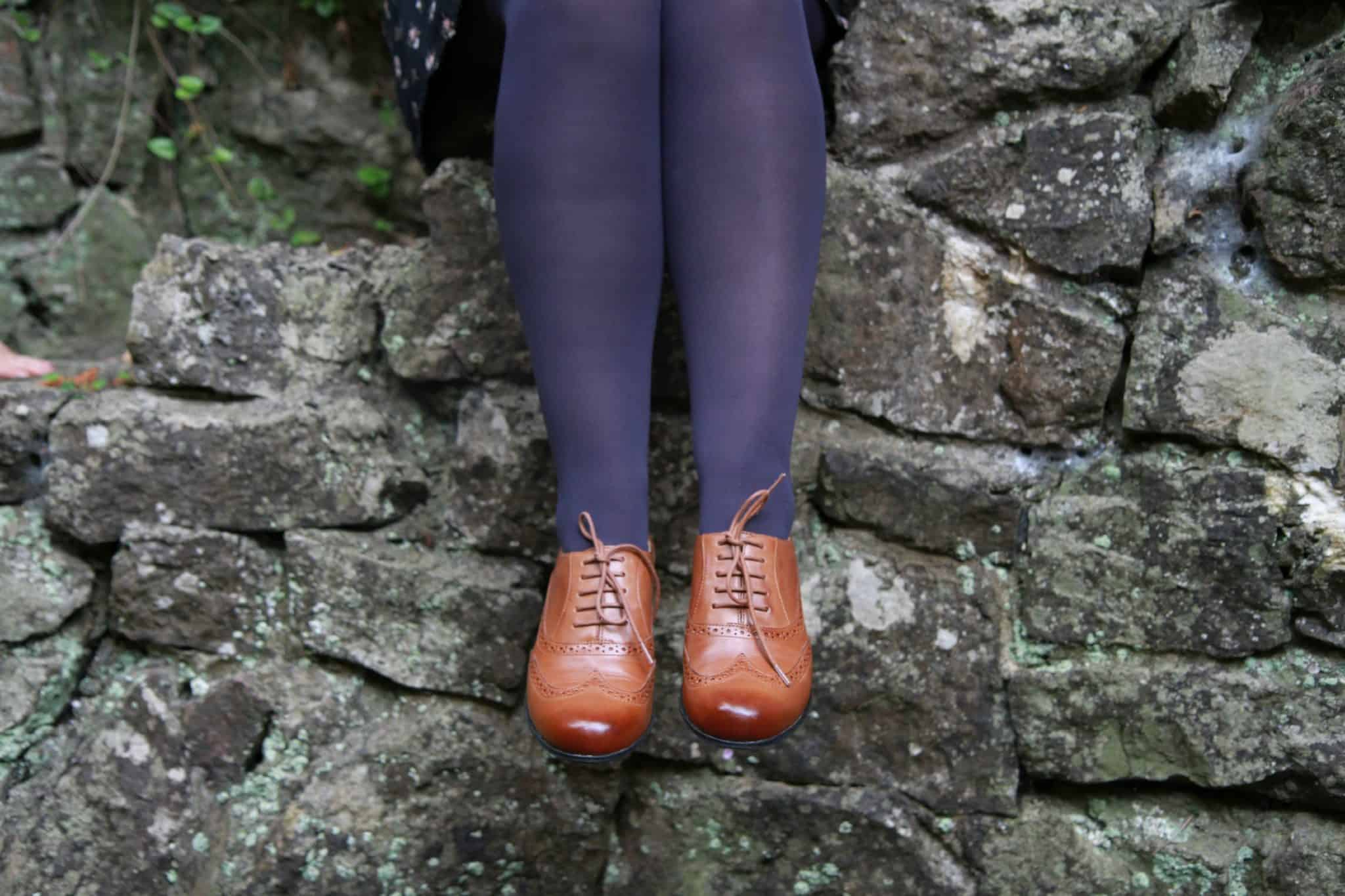 Tan leather brogues worn with a button through dress and navy blue tights