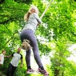 Swinging on a rope swing in a forest in Tintern-Wye Valley