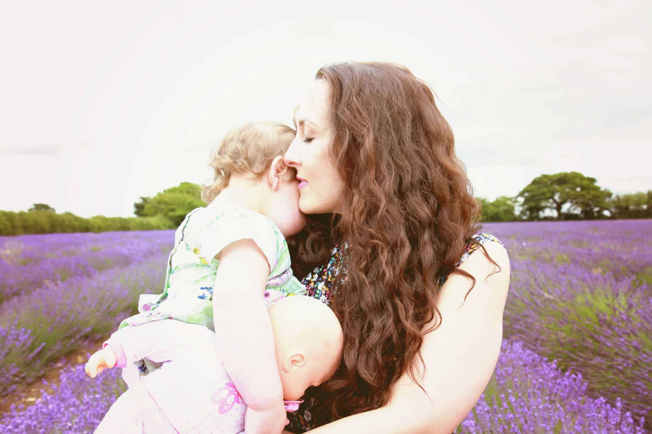 An image of a gentle mother holding a child in a field full of lavender.