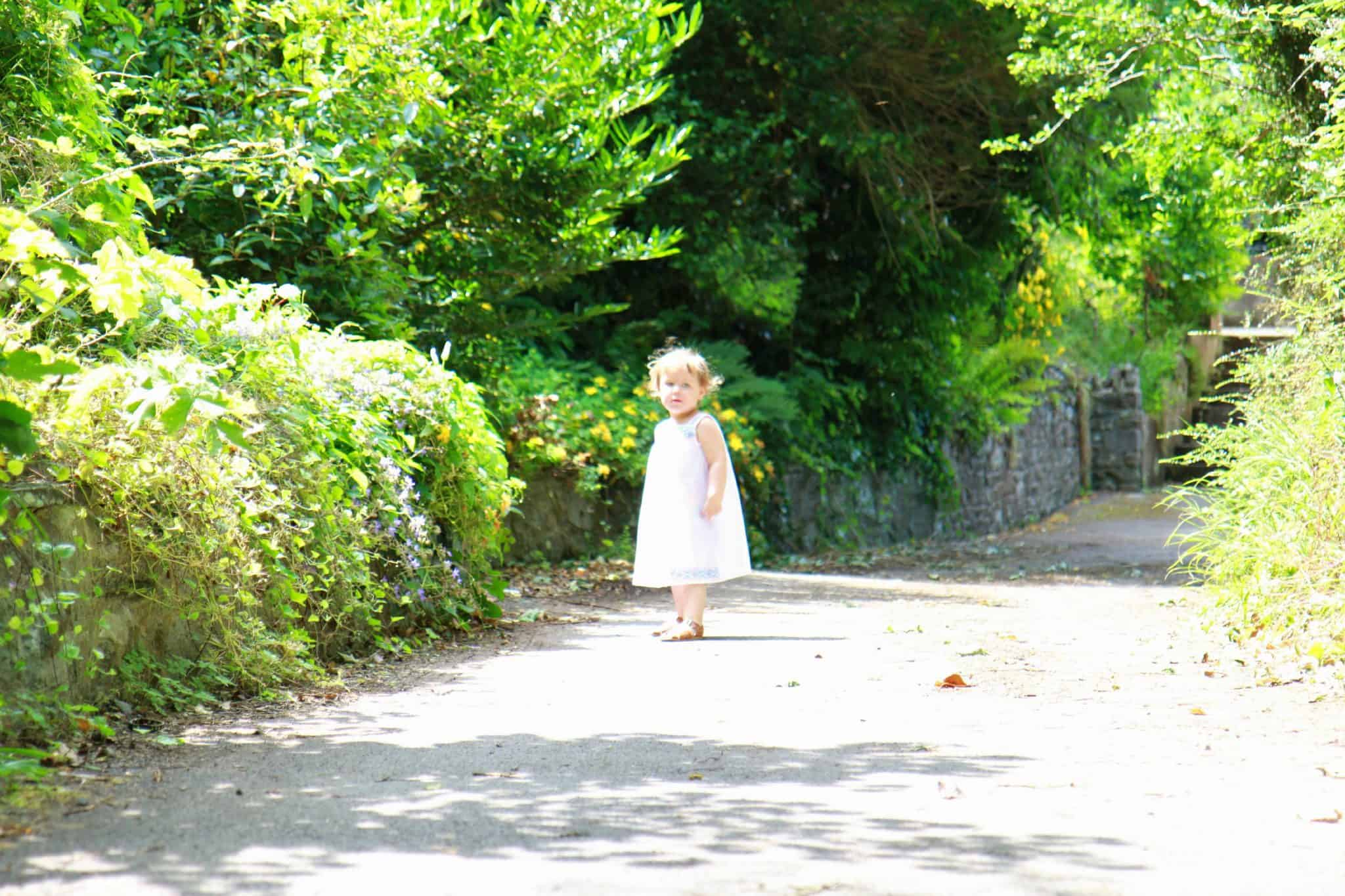 Little girl playing outside in embroidered sundress