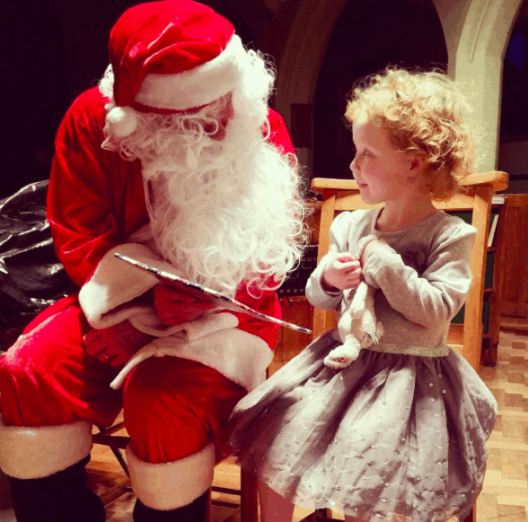 Little girl looking up at Santa