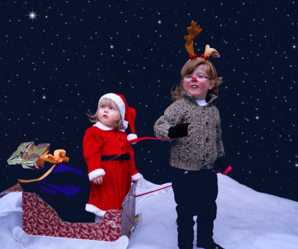 Two little girls dressed up on Santa's sleigh