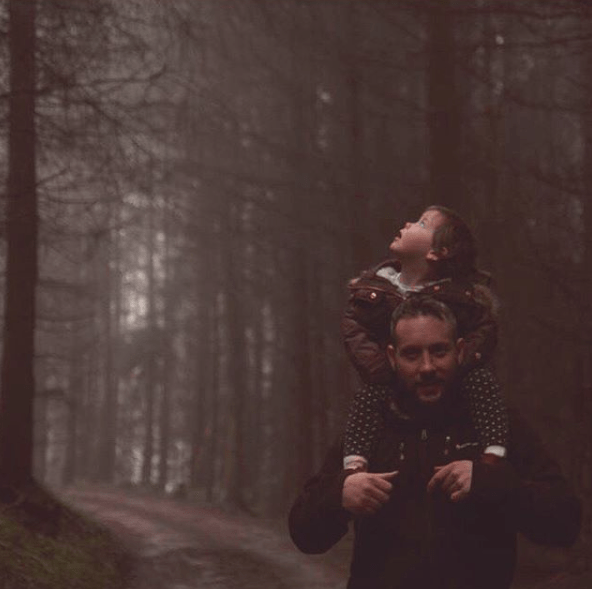 Little girl in the forest sitting on daddy's shoulders looking up in wonder at the trees