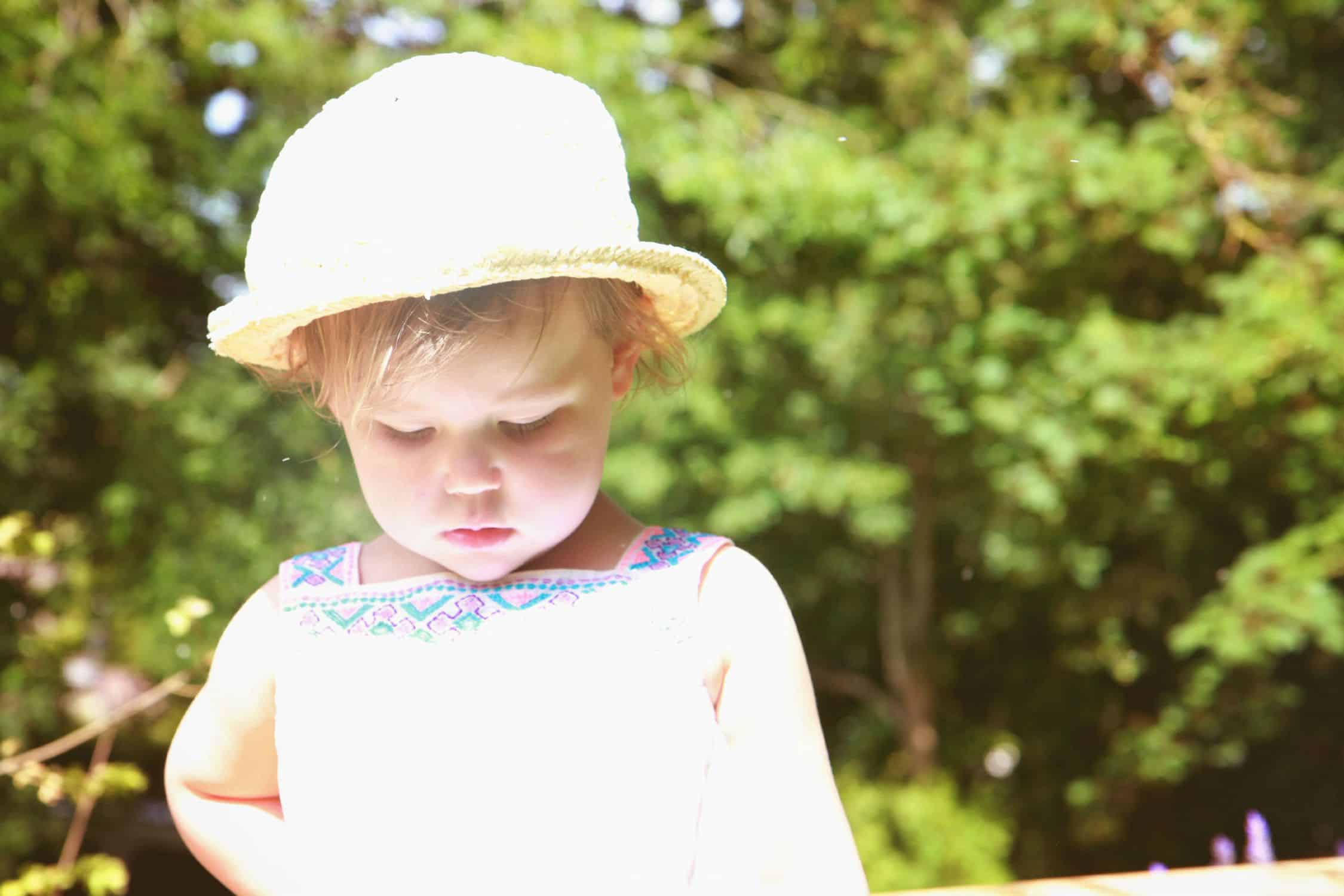Little girl in a hat in the sunlight