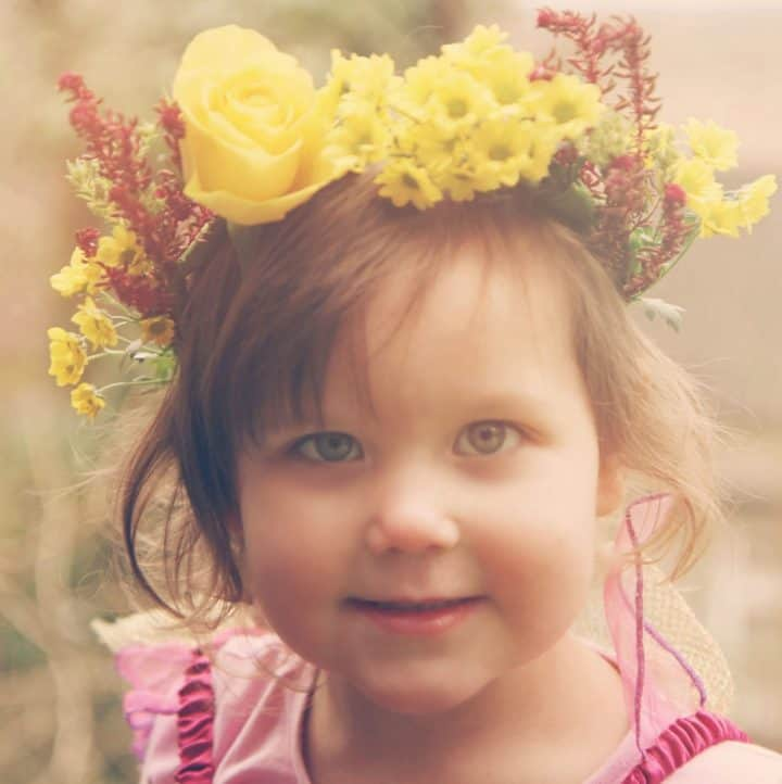 A little girl in a handmade beautiful flower crown made from fresh flowers