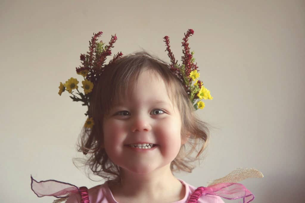 Little girl wearing a flower crown made from yellow daisies and heather