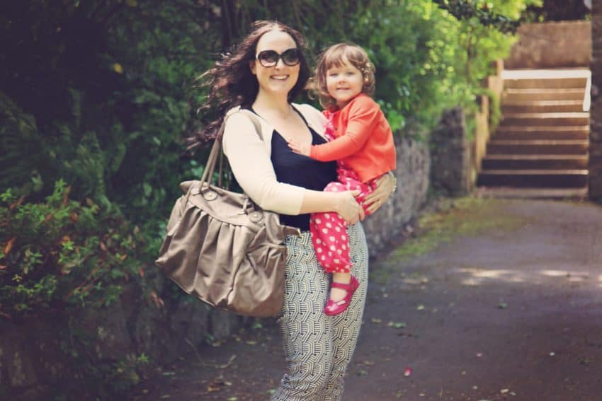 Mother holding a large changing bag and a toddler