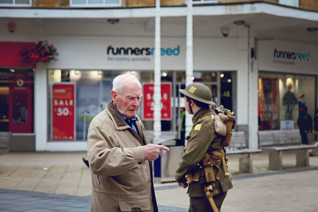 An older man inspects a card handed to him from one of the soldiers dressed to commeorate the solders who lost their lives in the battle of the somme