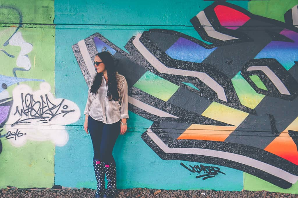 Graffiti wall, wearing Joules spotty navy and white neoprene wellies