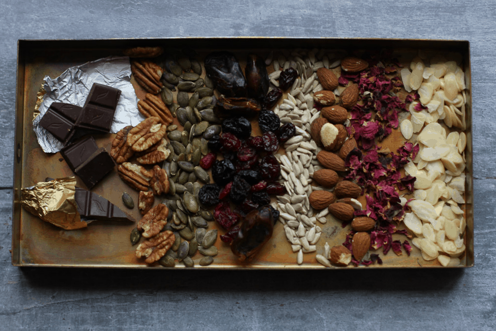 A tray of dark chocolate, fruits, nuts and seeds
