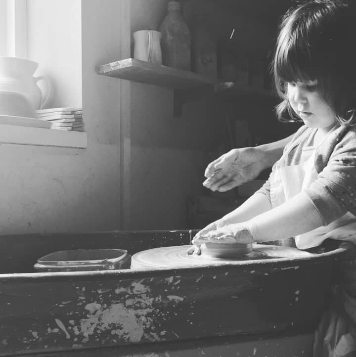 Little girl at pottery wheel