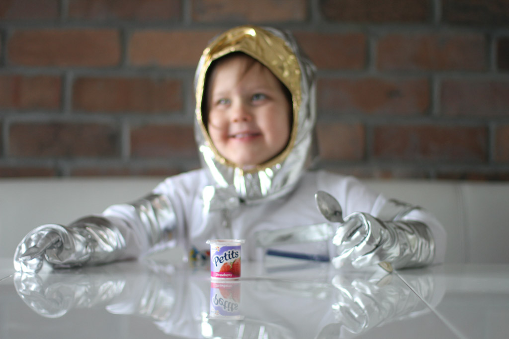 girl dressed as an astronaut sitting at a table eating a yoghurt