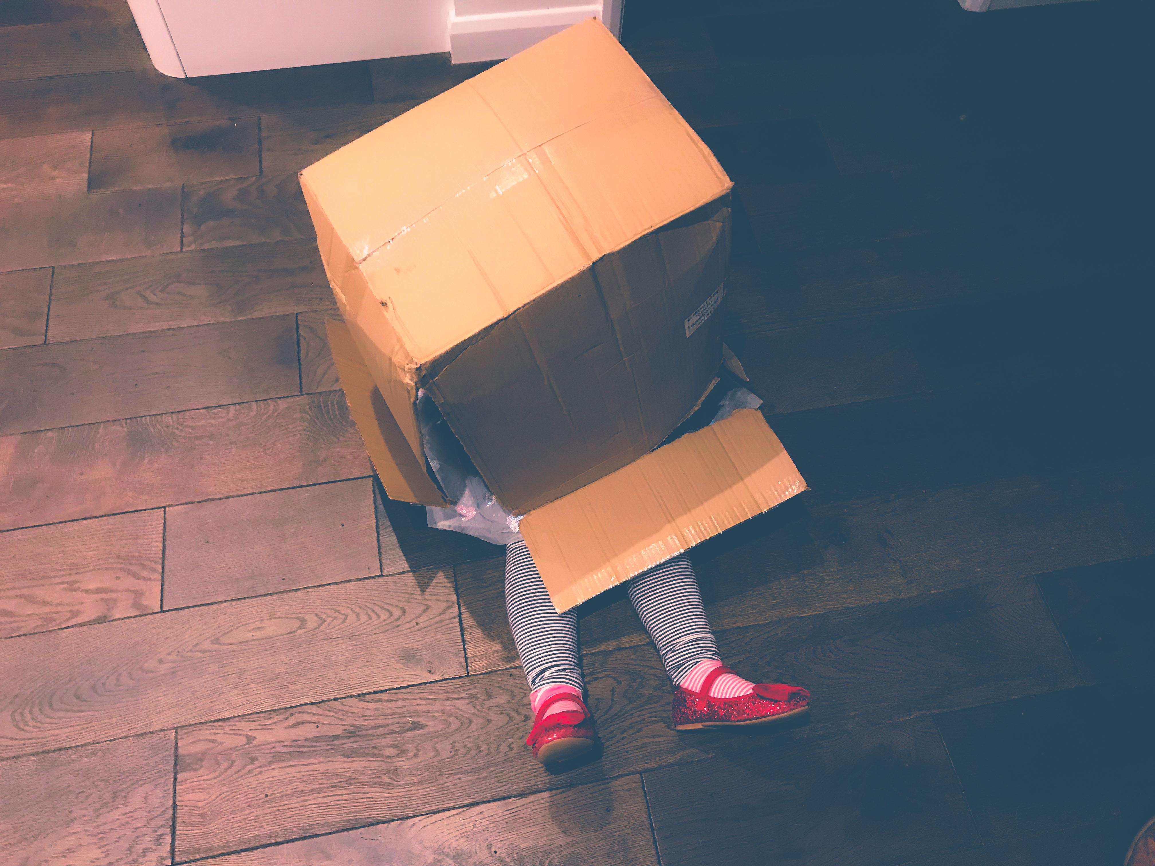 Little girl hiding in a cardboard box with her red shoes poking out