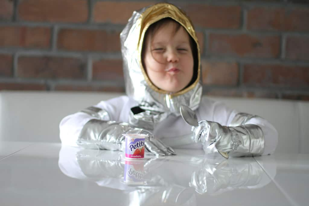 Girl in astronaut costume eating Petits Filous