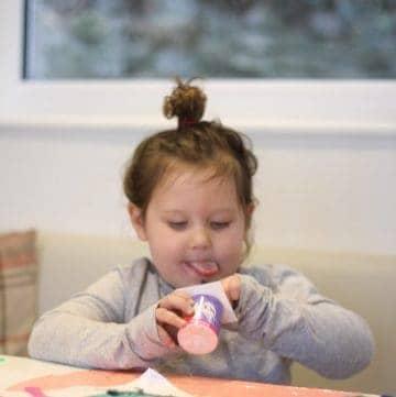 Little girl eating a pot of Petits Filous
