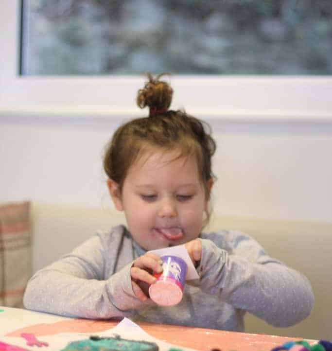 Little girl eating a pot of Petits Filous