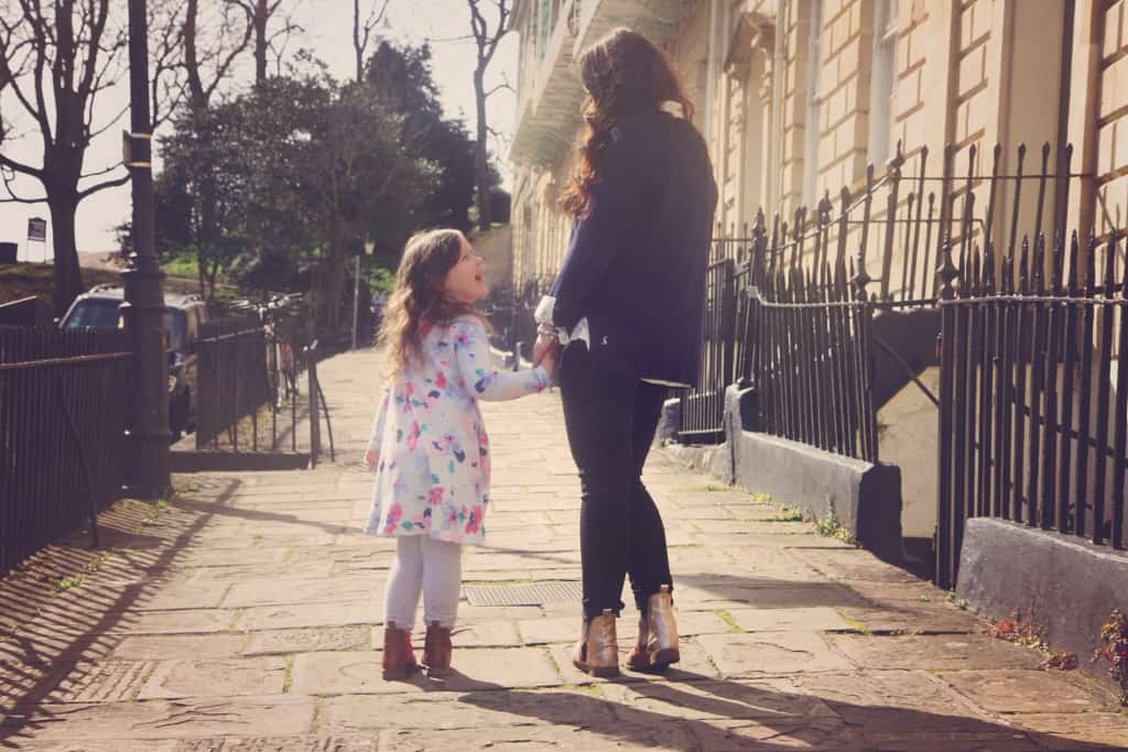 Mother and daughter holding hands, walking