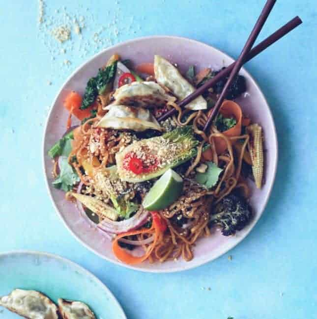 A plate of Vegan Pad Thai noodles and chop sticks with gyozu dumplings on the side