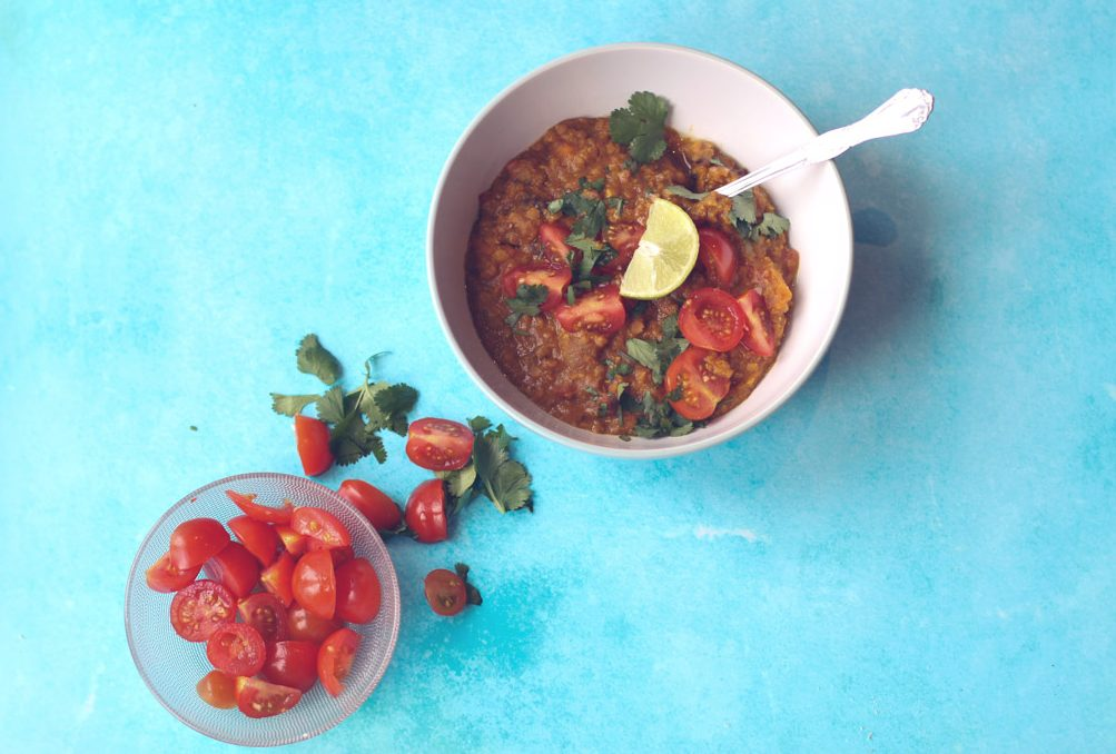 Sweet potato, coconut and tomato lentil dahl in a bowl beside a bowl of cherry tomatoes