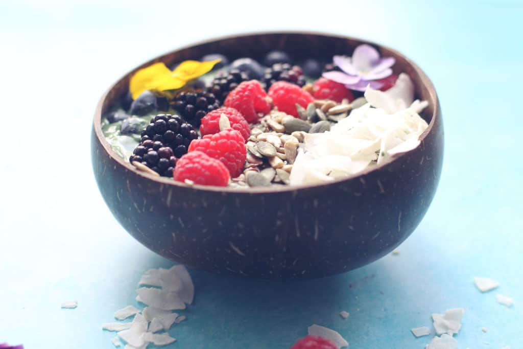 Half a coconut Green Smoothie Bowl topped with fresh fruit and coconut
