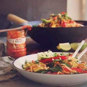 Vegetable stir-fry with a jar of chilli pesto