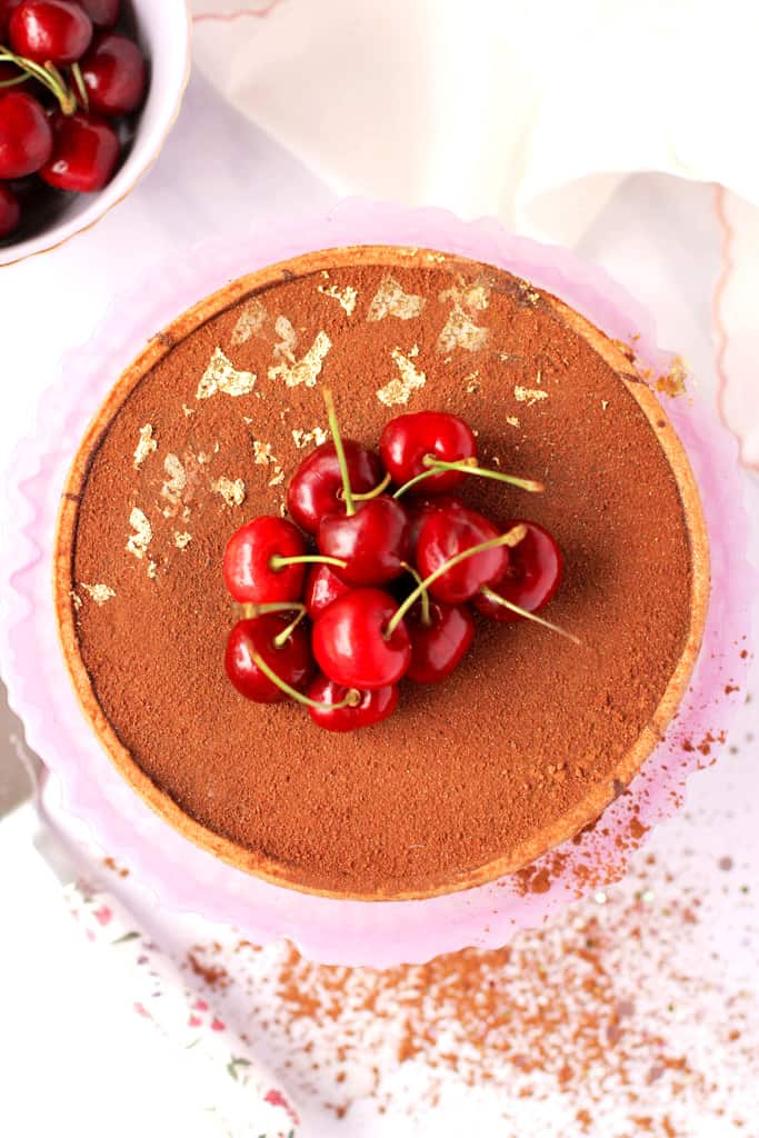 Overhead shot of a salted caramel chocolate tart topped with edible gold leaf and cherries