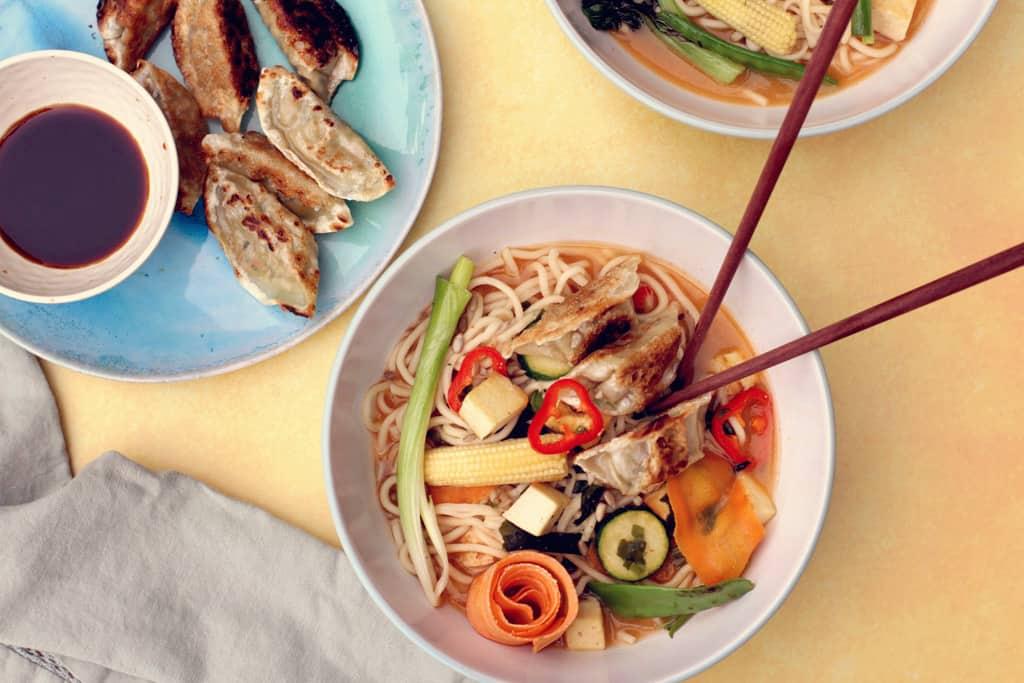 Overhead shot of vegetarian ramen with crispy tofu and gyoza dumplings