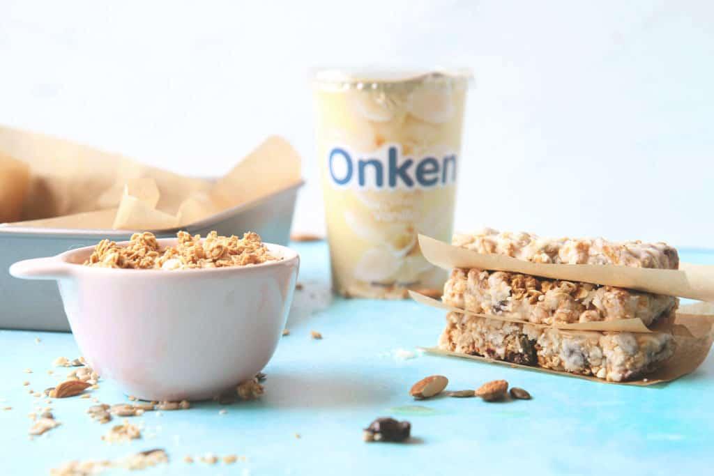 Side view of yoghurt coated granola bars with a pot of Onken yoghurt