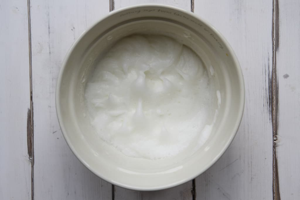 A mixing bowl with egg whites whipped to soft peaks