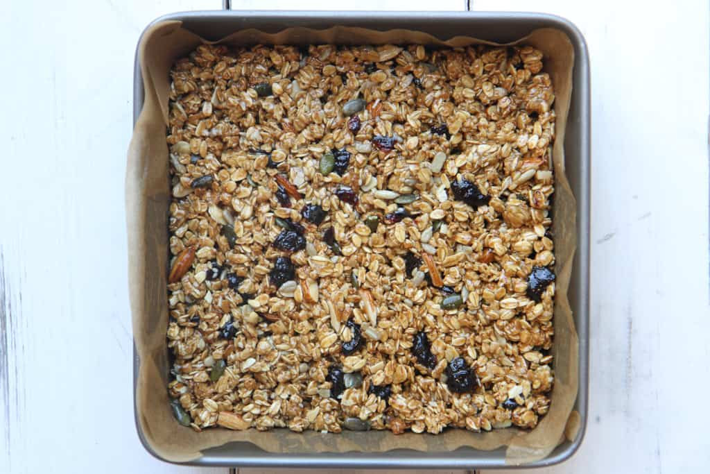 A square tin containing prepared mixture for granola bars
