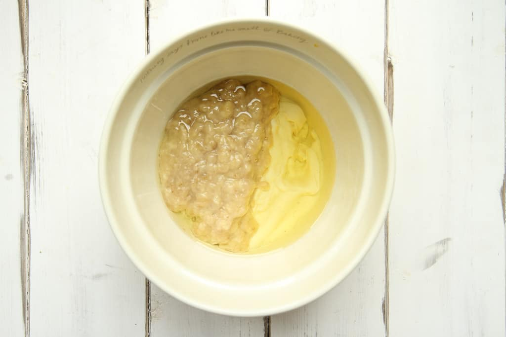 mashed bananas, vegetable oil and yoghurt in a mixing bowl