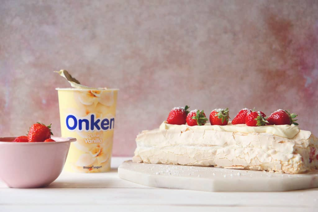 An Eton Mess Roulade topped with strawberries with an Onken yoghurt and cream filling