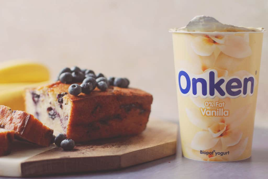 Baked blueberry banana bread with fresh blueberries on top, bananas in the background and a pot of Onken yoghurt to the side