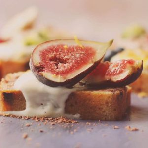 A slice of banana bread topped with yoghurt and a fig cut in half
