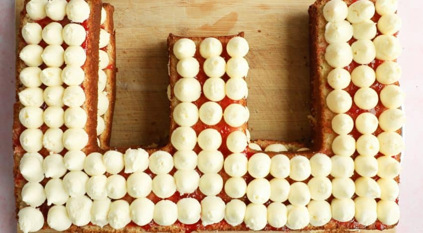 A letter E shaped cake topped with buttercream icing