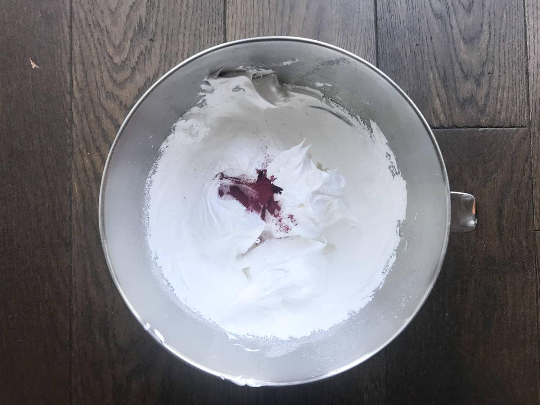 Adding pink powder to meringue mixture