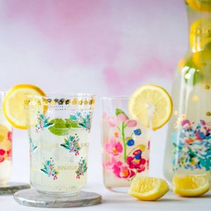 Glasses of lemon cordial with a pitcher of lemon cordial in the background