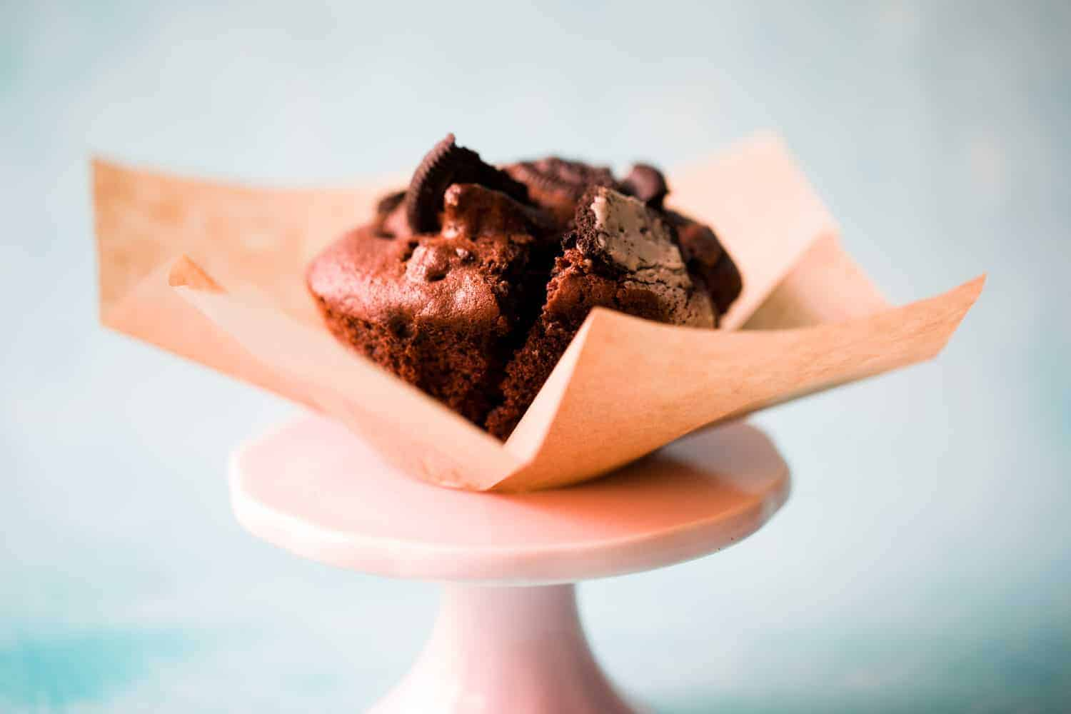 Side view of an Oreo muffin in a brown muffin case on top of a small pink cake stand