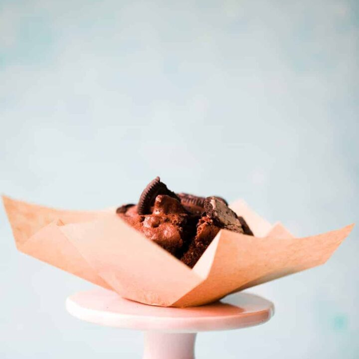 An Oreo Muffin in a brown muffin case on a small pink cake stand