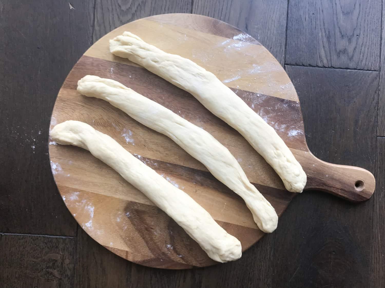 A chopping board with three pieces of brioche dough
