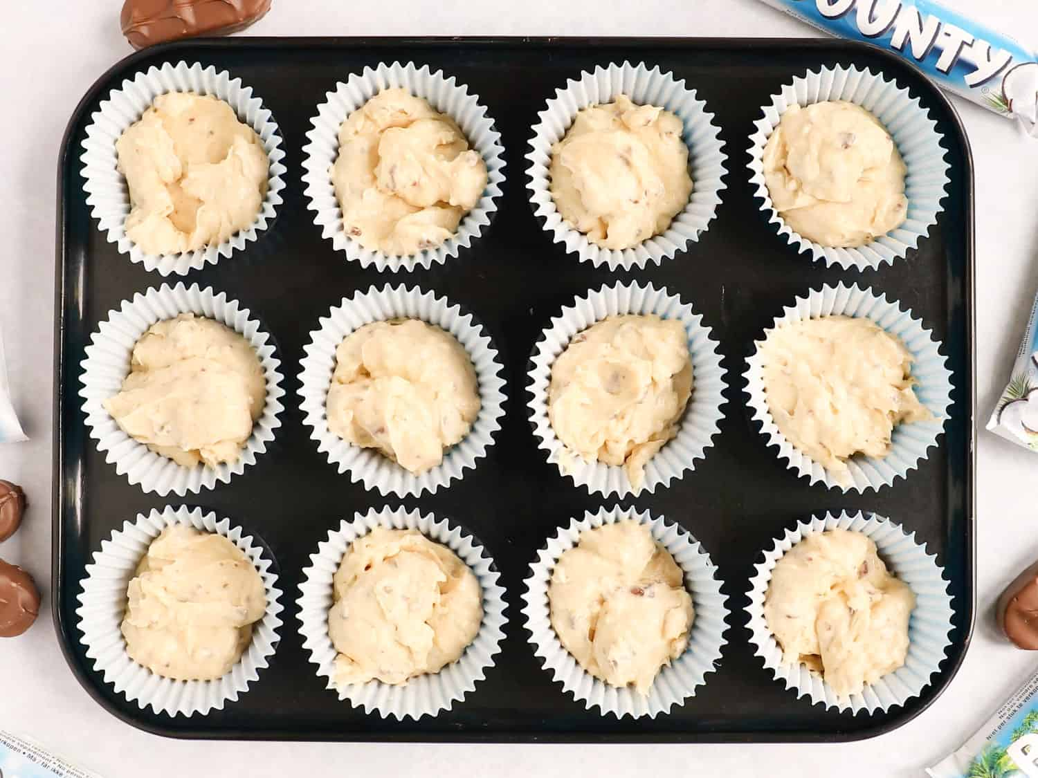 A baking tray filled with 12 cupcake cases containing cupcake batter