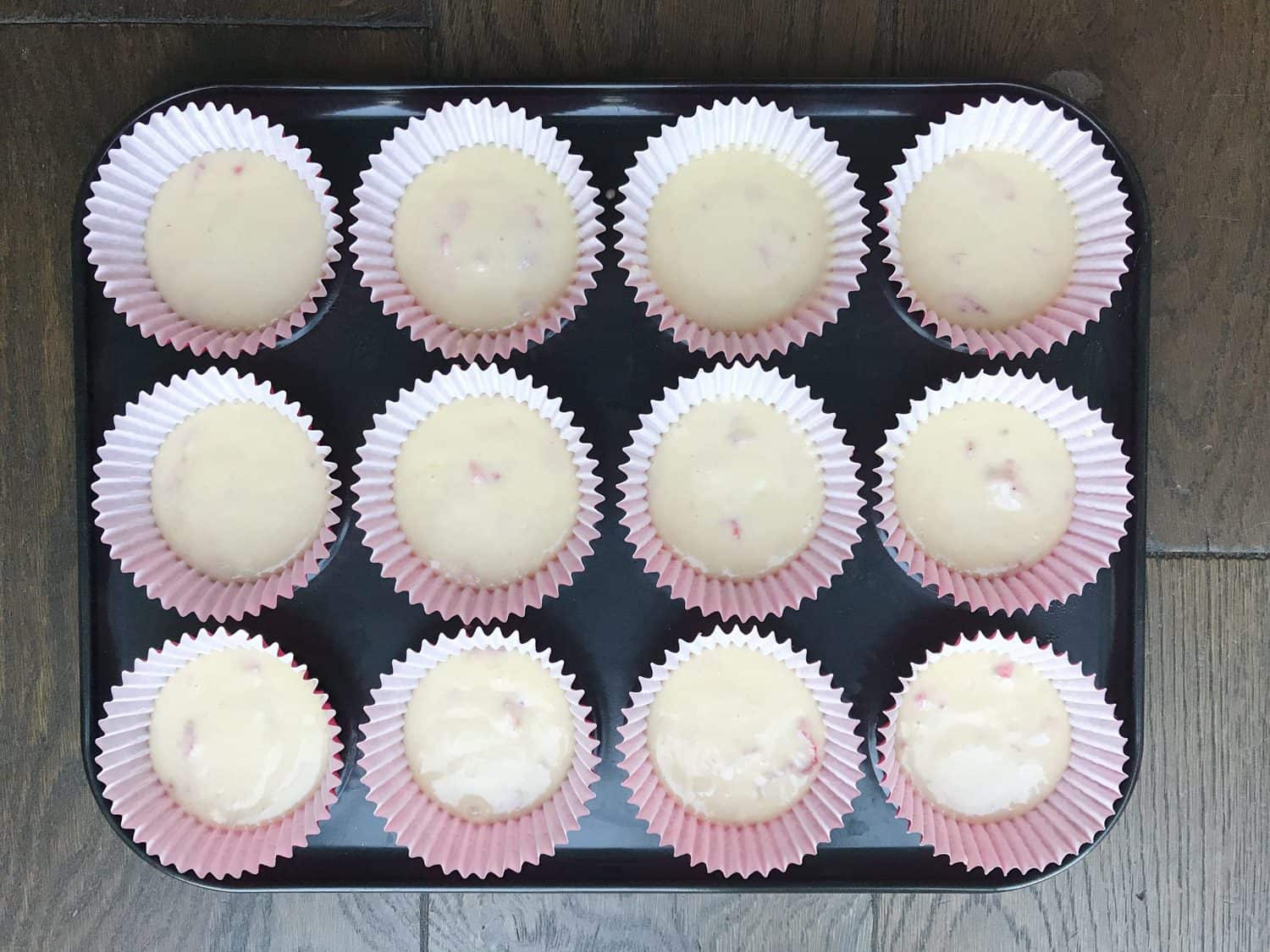 A baking tray with 12 cupcake cases filled half full