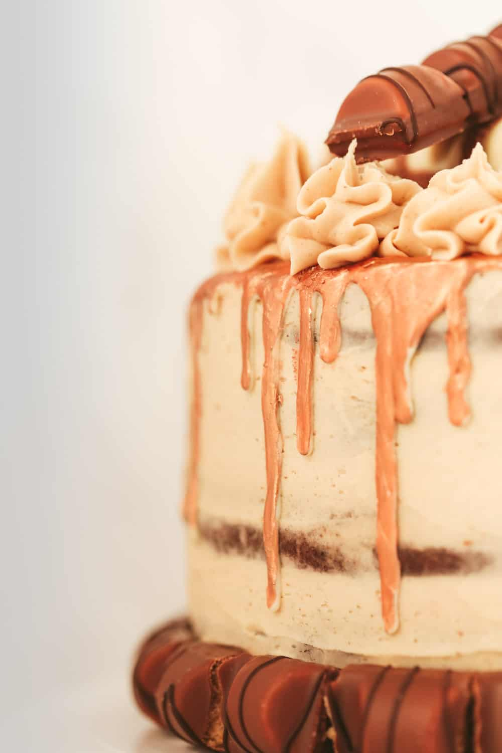 Side profile of a Kinder Cake with nutella buttercream covering adn a white chocolate drip that has been painted gold. Around the bottom of the cake is Kinder Bueno pieces.