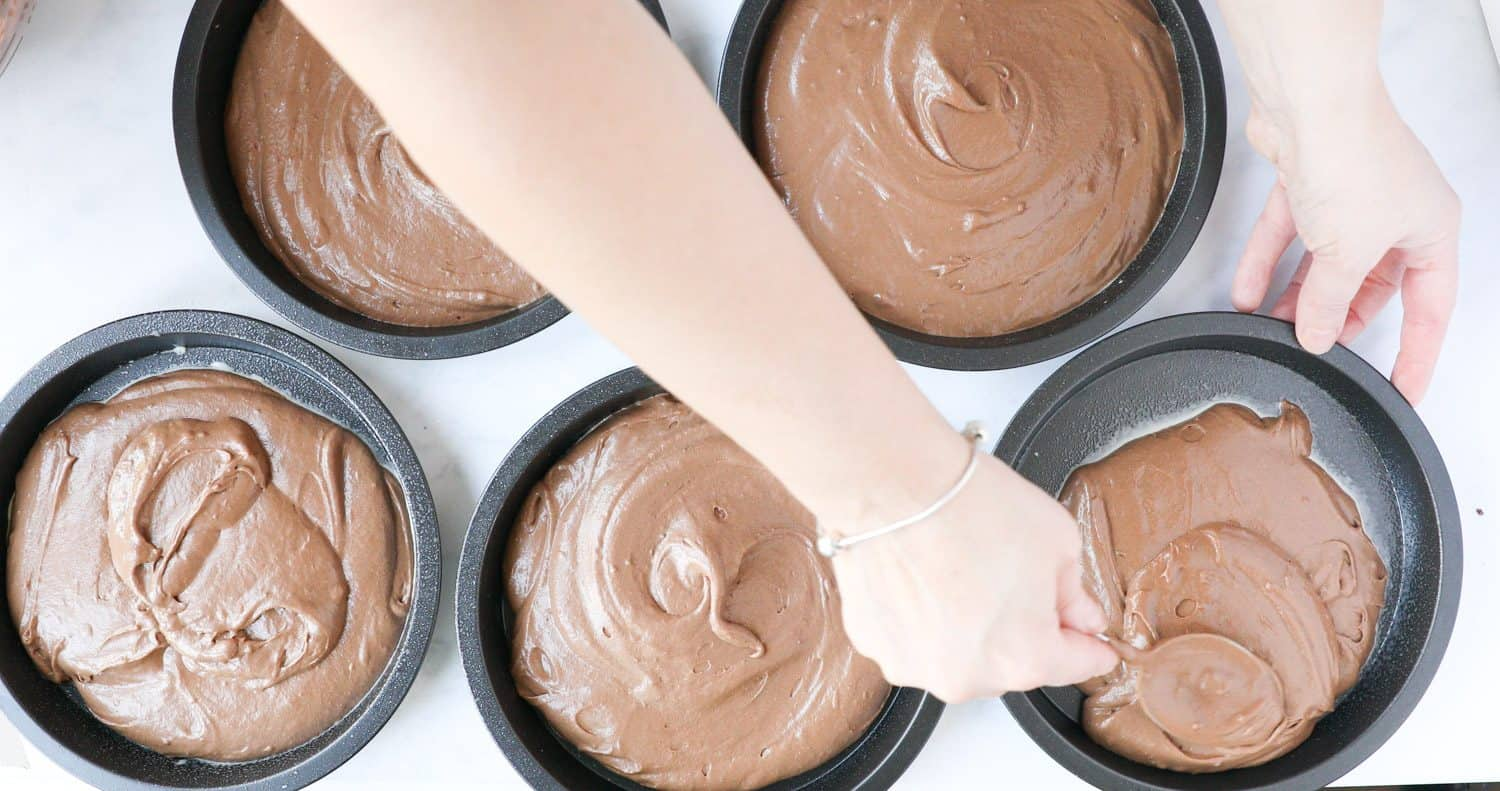 5 shallow cake tins with chocolate cake batter being poured into them