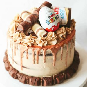 A chocolate layer cake covered with nutella buttercream and decorated with Kinder chocolate