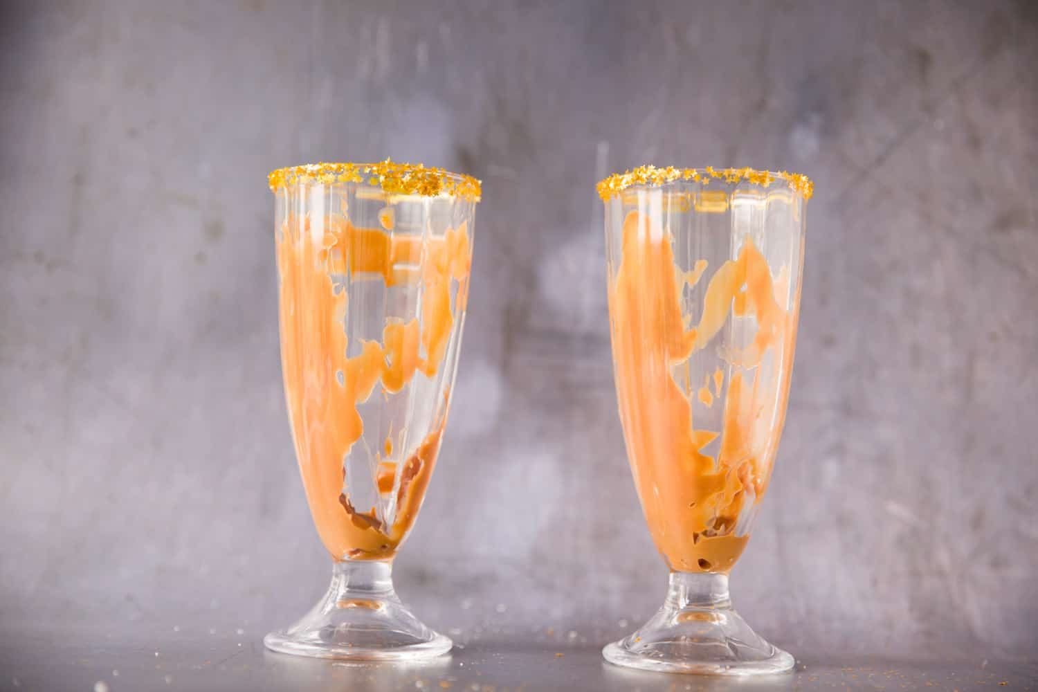 Two glasses filled with caramel sauce
