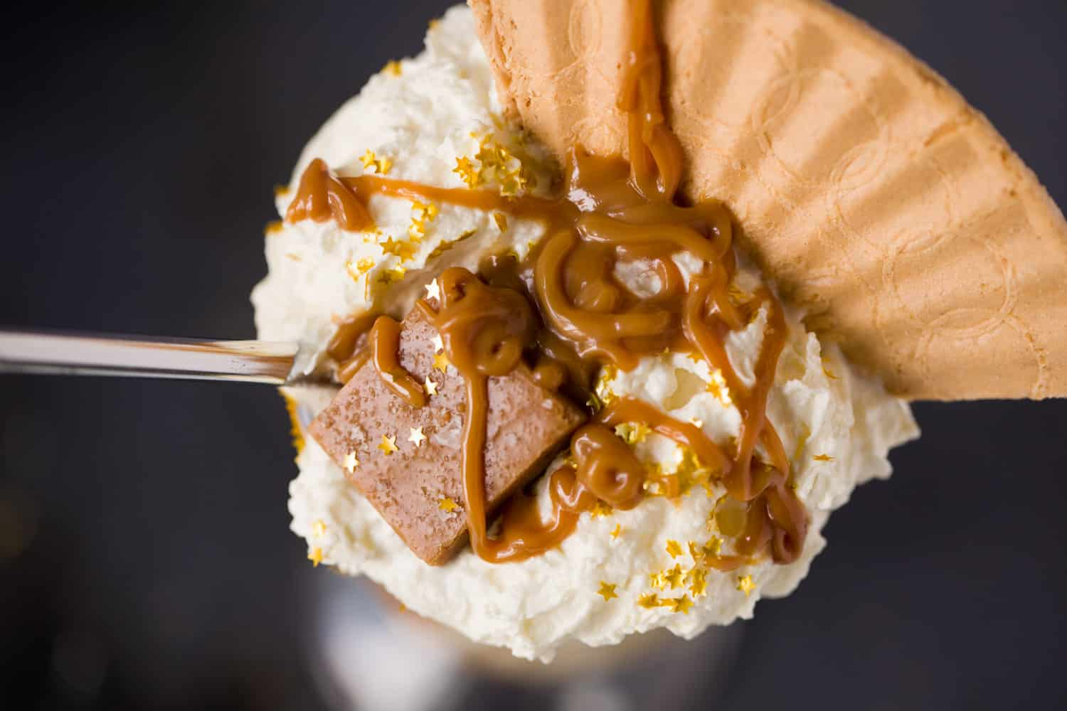 Overhead view of a milkshake in a glass, there is whipped cream on top, a wafer, salted caramel sauce and a piece of fudge