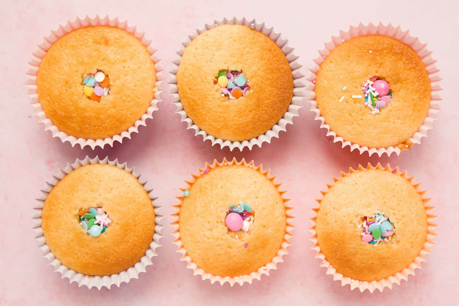Overhead shot of six cupcakes with the centres carved out and filled with sprinkles